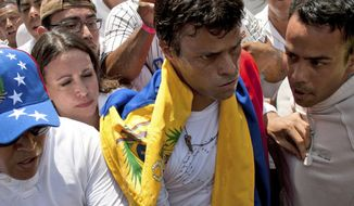 FILE - In this Feb 18, 2014 file photo, opposition leader Leopoldo Lopez, second from right, draped in a Venezuelan national flag, is flanked by Jose Rafael Perez, right, just before Lopez surrenders to national guards, in Caracas, Venezuela. Lopez's wife Lilian Tintori stood outside a military hospital in Caracas late Wednesday, May 3, 2017, after an unconfirmed report on social media said her husband was taken there with a medical emergency. (AP Photo/Juan Manuel Hernandez, File)
