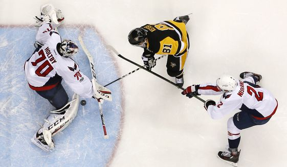 Washington Capitals goalie Braden Holtby (70) stops a shot by Pittsburgh Penguins' Phil Kessel (81) with Matt Niskanen (2) defending during the second period of Game 4 in an NHL Stanley Cup Eastern Conference semifinal hockey game in Pittsburgh, Wednesday, May 3, 2017. The Penguins won 3-2. (AP Photo/Gene J. Puskar)