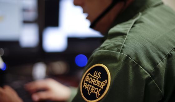 File- In this June 5, 2014 file photo, a Border Patrol agent uses a headset and computer to conduct a long distance interview by video from a facility in San Diego. A government report says inefficient computer systems and a lack of exit screening hamper U.S. authorities' efforts to track the number of foreigners who overstay their visas. The Department of Homeland Security's Office of Inspector General said Thursday, May 4, 2017, that immigration agents and analysts need better and more integrated computer systems to check visitors' immigration status. (AP Photo/Gregory Bull, File)