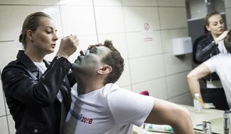 In this photo taken on Thursday, April 27, 2017, Yulia, wife of Russian opposition leader Alexei Navalny treats him after unknown attackers doused him with green antiseptic outside a conference venue in Moscow, Russia. Navalny, who authored a documentary about the Russian prime minister's alleged corrupt wealth that was viewed more than 20 million times online, was the key force behind nationwide anti-government rallies in March, Russia's largest and most widespread in years. (Evgeny Feldman/Pool Photo via AP)