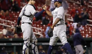 Milwaukee Brewers relief pitcher Neftali Feliz, right, and catcher Jett Bandy celebrate following a 5-4 victory over the St. Louis Cardinals in a baseball game Thursday, May 4, 2017, in St. Louis. (AP Photo/Jeff Roberson)