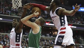 Boston Celtics forward Jonas Jerebko (8), from Sweden, center, draws a foul as Washington Wizards center Ian Mahinmi (28), left, and guard John Wall (2) defend during the first half of a second-round NBA playoff series basketball game, Thursday, May 4, 2017, in Washington. (AP Photo/Andrew Harnik)