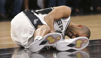 In this Wednesday, May 3, 2017 photo, San Antonio Spurs' Tony Parker holds his left leg after getting injured in the second half of Game 2 of the Western Conference semifinals at the AT&T Center against the Houston Rockets in San Antonio. The Spurs announced on Thursday, May 4, 2017,  that Parker has a ruptured quadriceps tendon in his left leg. (Jerry Lara/The San Antonio Express-News via AP)