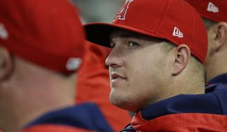 Los Angeles Angels outfielder Mike Trout sits in the dugout with teammates during the first inning of a baseball game against the Seattle Mariners, Thursday, May 4, 2017, in Seattle. Trout was not in the starting lineup. (AP Photo/Ted S. Warren)
