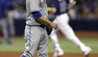 Toronto Blue Jays starting pitcher Marco Estrada, foreground, walks back to the mound as Tampa Bay Rays' Colby Rasmus runs around the bases after Rasmus hit a two-run home run during the sixth inning of a baseball game Saturday, May 6, 2017, in St. Petersburg, Fla. (AP Photo/Chris O'Meara)