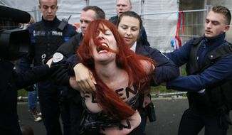 A Femen activist is led away by French police in Henin-beaumont, northern France, Sunday, May 7, 2017. Voters across France are choosing a new president in an unusually tense and important election that could decide Europe's future, making a stark choice between pro-business progressive candidate Emmanuel Macron and far-right populist Marine Le Pen. (AP Photo/Francois Mori)