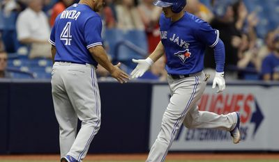 Toronto Blue Jays' Darwin Barney, right, shakes hands with third base coach Luis Rivera after his home run off Tampa Bay Rays starting pitcher Alex Cobb during the eighth inning of a baseball game, Sunday, May 7, 2017, in St. Petersburg, Fla. (AP Photo/Chris O'Meara)
