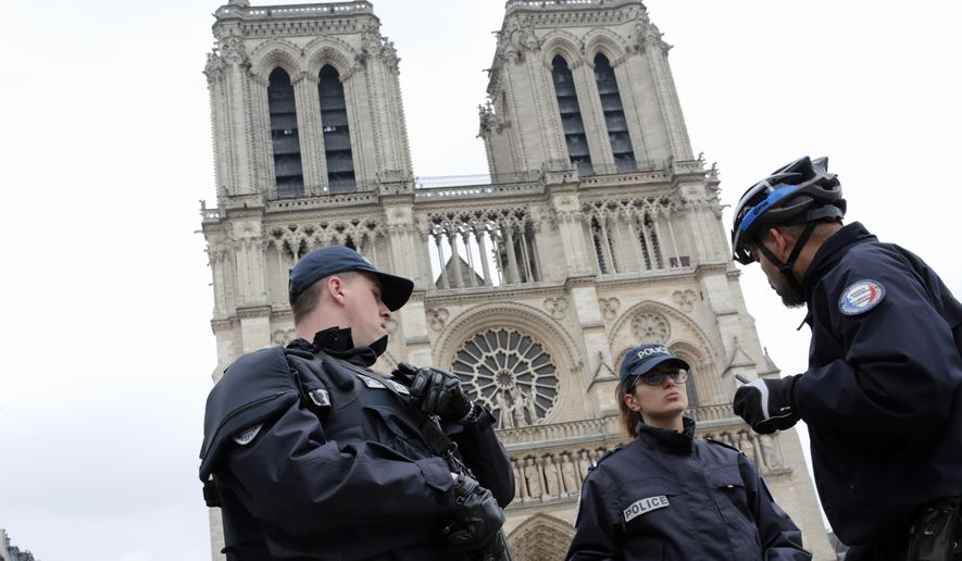 French police officers patrol outside Notre Dame Cathedral Sunday, May 7, 2017 in Paris. French voters decided Sunday whether to back pro-business independent Emmanuel Macron or far-right populist Marine Le Pen as their next president, casting ballots in an unusually tense and important presidential election that also could decide Europe's future. (AP Photo/Buhran Ozbiblici) ** FILE **
