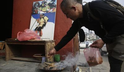 A family member lights incense in front of a photograph of Nepalese climber Min Bahadur Sherchan during his funeral in Kathmandu, Nepal, Sunday, May 7, 2017. The 85-year-old Nepali man died while attempting to regain his title as the oldest person to climb Mount Everest, officials said. Sherchan died at the Everest base camp on Saturday evening. (AP Photo/Niranjan Shrestha)