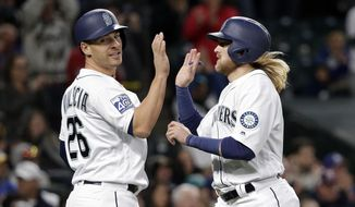 Seattle Mariners' Danny Valencia, left, and Taylor Motter share congratulations after both scored on a single by Ben Gamel against the Texas Rangers in the seventh inning of a baseball game Saturday, May 6, 2017, in Seattle. (AP Photo/Elaine Thompson)