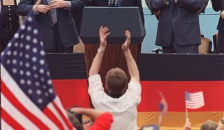 "President Reagan gives a thumbs-up sign after his speech in front of the Brandenburg Gate in West Berlin, where he said ""Mr. Gorbachev, tear down this wall!"" June 12, 1987. Applauding Reagan are West German Chancellor Helmut Kohl, right, and West German Parliament President Philipp Jenninger, left.    Associated Press photo"