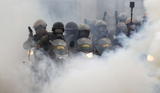 Bolivarian National Guards block students attempting to march to the Education Ministry amid tear gas in Caracas, Venezuela, Monday, May 8, 2017. The protest movement against President Nicolas Maduro, that has drawn masses of people into the streets nearly every day since March, has left some three dozen dead. (AP Photo/Fernando Llano)