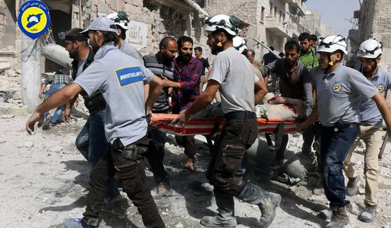 In this photo provided by the Syrian Civil Defense White Helmets, rescue workers work the site of airstrikes in  the al-Sakhour neighborhood of the rebel-held part of eastern Aleppo, Syria, Wednesday Sept. 21, 2016. Ibrahim Alhaj, a member of the volunteer first responders known as the Syria Civil Defense, said 24 people were killed in a series of bombings in several parts of the besieged city Aleppo on Wednesday.  (Syrian Civil Defense White Helmets via AP)
