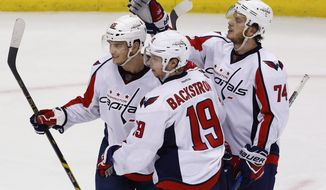 Washington Capitals' Andre Burakovsky (65) celebrates his second goal of the game with Nicklas Backstrom (19) and John Carlson (74) during the third period of Game 6 in an NHL Stanley Cup Eastern Conference semifinal hockey game against the Pittsburgh Penguins in Pittsburgh, Monday, May 8, 2017. The Capitals won 5-2. (AP Photo/Gene J. Puskar)