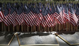 U.S. flags flutter over some of the names at the Peace Officers Memorial in Sacramento, Calif., in this Monday, May 8, 2017, file photo. The names of 10 officers who lost their lives in the line of duty in 2016 names were added to the memorial during the annual Peace Officers Memorial ceremony. (AP Photo/Rich Pedroncelli)