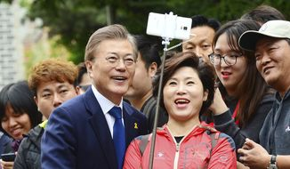 South Korean presidential candidate Moon Jae-in, front left, of the Democratic Party takes pictures with a supporter after voting for a presidential election at a junior high school in Seoul, South Korea, Tuesday, May 9, 2017. South Koreans voted Tuesday for a new president, with victory widely predicted for a liberal candidate who has pledged to improve ties with North Korea, re-examine a contentious U.S. missile defense shield and push sweeping economic changes. (Park Young-tae/Newsis via AP)