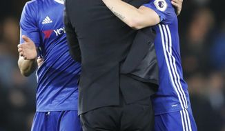 Chelsea's manager Antonio Conte hugs Chelsea's Cesc Fabregas, right, and Chelsea's Diego Costa, left, at the end of the English Premier League soccer match between Chelsea and Middlesbrough at Stamford Bridge stadium in London, Monday, May 8, 2017. Chelsea won the match 3-0. (AP Photo/Frank Augstein)