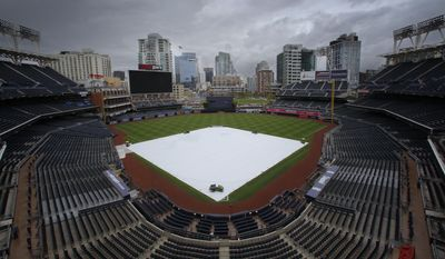 The a tarp covers the infield at Petco Park, Sunday, May 7, 2017, in San Diego. A spring storm hit Southern California on Sunday with gusty winds, thunderstorms and pea-size hail stones, prompting everything from the cancellation of a baseball game to the sight of celebrities at a red-carpet ceremony scrambling for cover. (Nelvin C. Cepeda/The San Diego Union-Tribune via AP)