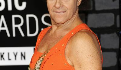 FILE - In this Aug. 25, 2013 file photo, Richard Simmons arrives at the MTV Video Music Awards in the Brooklyn borough of New York.  Simmons sued the National Enquirer, its online outlet and its parent company for libel on Monday, May 8, 2017, over stories that claimed he is living as a transgender woman. Simmons' lawsuit states the Enquirer based its stories on a man who has tried to blackmail him for years. National Enquirer publisher, American Media, Inc., said Monday that it is standing by its reporting. (Photo by Evan Agostini/Invision/AP, File)