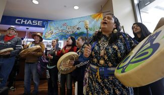 Roxanne White, right, a member of the Yakama Nation, sings during a protest inside a Chase bank branch Monday, May 8, 2017, in Seattle. Climate activists opposed to oil pipeline projects demonstrated at several JPMorgan Chase bank locations in Seattle on Monday, calling on the bank not to do business with TransCanada, the company pushing for the Keystone XL oil pipeline. (AP Photo/Elaine Thompson)