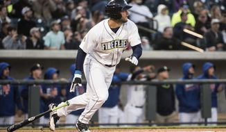 FILE - In this April 6, 2017, file photo, Columbia Fireflies' Tim Tebow watches his home run during his first at-bat, during the team's minor league baseball game against the Augusta GreenJackets, in Columbia, S.C. After his first month in pro baseball, the New York Mets prospect and former Heisman winner seems to be getting more comfortable on the baseball field. (AP Photo/Sean Rayford, File)