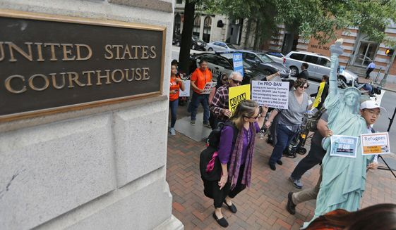 Protesters hold signs and march outside the US 4th Circuit Court of Appeals in Richmond, Va., Monday, May 8, 2017. (AP Photo/Steve Helber) ** FILE **
