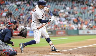 Houston Astros' Carlos Correa, right, hits a three-run home run as Atlanta Braves catcher Tyler Flowers reaches for the pitch during the first inning of a baseball game, Tuesday, May 9, 2017, in Houston. (AP Photo/David J. Phillip)