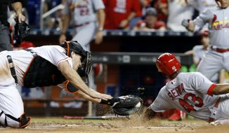 Miami Marlins catcher J.T. Realmuto, left, is unable to tag out St. Louis Cardinals' Magneuris Sierra (43) during the ninth inning of a baseball game, Tuesday, May 9, 2017, in Miami. The Cardinals defeated the Marlins 6-5. (AP Photo/Wilfredo Lee)