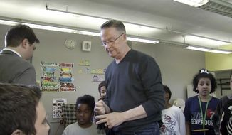 """In this Monday, May 8, 2017 image made from a video by KCRG, U.S. Rep. Rod Blum, center, walks out of a televised interview with Josh Scheinblum in front of a group of schoolchildren in Dubuque, Iowa, when pressed about screening attendees to his public meetings. The second-term Republican and member of the conservative House Freedom Caucus later said he had been """"ambushed"""" by the television news reporter who was questioning him. (KCRG via AP)"""