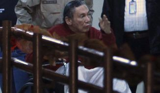 FILE - This Dec. 11, 2011 file photoshows Panama's former strongman Manuel Noriega transported in a wheelchair, pushed by a police officer inside El Renacer prison, on the outskirts of Panama City. A Panamanian judge, on Tuesday, May 9, 2017, has extended the house arrest conditions for Noriega to one year following his surgery to remove a benign brain tumor. (AP Photo/Esteban Felix, File)