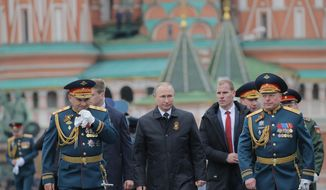 Russian Defence Minister Sergei Shoigu, left, Russian President Vladimir Putin, center, and Russian army Gen. Oleg Salyukov, right, walk along the Red Square during the Victory Day military parade to celebrate 72 years since the end of WWII and the defeat of Nazi Germany, in Moscow, Russia, on Tuesday, May 9, 2017. (Yuri Kochetkov/Pool photo via AP)