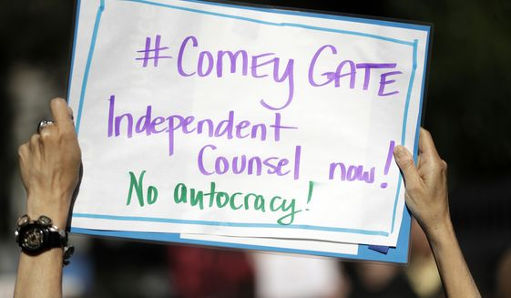A protester waves a sign outside of the offices of Sen. Dianne Feinstein, D-Calif., Wednesday, May 10, 2017, in San Francisco. Dozens of protesters chanted slogans outside of Feinstein's office in protest of President Donald Trump's firing of FBI director James Comey. (AP Photo/Marcio Jose Sanchez)