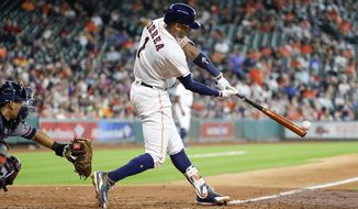 Houston Astros' Carlos Correa (1) hits a two-run double as Atlanta Braves catcher Kurt Suzuki works behind the plate during the fifth inning of a baseball game Wednesday, May 10, 2017, in Houston. (AP Photo/David J. Phillip)