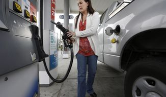 FILE - In this Nov. 12, 2014 file photo, Lydia Holland replaces the gas nozzle after filling up at a gas station in Sacramento, Calif. A measure that would impose a hefty tax on carbon pollution and use much of the revenue to give money back to taxpayers is scheduled for a hearing in a California state Senate committee Wednesday, May 10, 2017. (AP Photo/Rich Pedroncelli, File)
