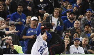 Toronto Blue Jays third baseman Darwin Barney (18) catches a foul ball off the bat of Cleveland Indians third baseman Jose Ramirez (11) during seventh inning baseball action in Toronto on Wednesday, May 10, 2017. (Nathan Denette/The Canadian Press via AP)