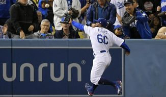 Los Angeles Dodgers left fielder Andrew Toles tries to catch a ball hit for a ground-rule-double by Pittsburgh Pirates' Andrew McCutchen during the seventh inning of a baseball game, Tuesday, May 9, 2017, in Los Angeles. Toles was injured after running into the wall, and left the game. (AP Photo/Mark J. Terrill)