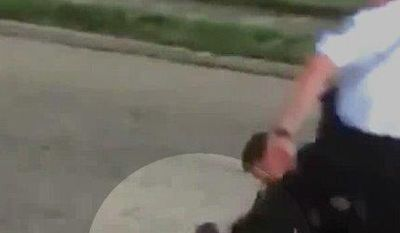 """This April 8, 2017, image made from a video and obtained from the Columbus Police Department through a records request by the Associated Press shows a Columbus officer restraining a prone man and preparing to handcuff him as a second officer appears to kick him in the head. The officer used """"unreasonable"""" force that wasn't part of his training when subduing the restrained suspect in a way that appeared to show him kicking the suspect in the head, police in Ohio said Wednesday, May 10. The highlighted circle in the image was added by source. (Columbus Police Department via AP)"""