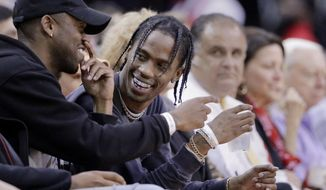 FILE - In this April 5, 2017, file photo, rap artist Travis Scott, center, reacts during an NBA basketball game between the Houston Rockets and Denver Nuggets in Houston. Scott and the Rockets will have a special treat for fans attending Game 6 of the Western Conference semifinals on Thursday night May 11. Everyone will receive exclusive t-shirts designed as part of a collaboration between the Houston rapper and the team. (AP Photo/Michael Wyke, File)