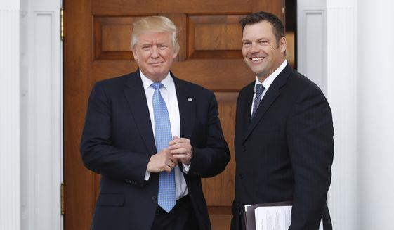 In this Nov. 20, 2016, file photo, Kansas Secretary of State Kris Kobach, right, holds a stack of papers as he meets with President-elect Donald Trump at the Trump National Golf Club Bedminster clubhouse in Bedminster, N.J. A federal judge ordered Kobach to disclose as part of a lawsuit challenging the state's voter registration requirements proposed changes to a federal voting law that he was photographed taking to the meeting. U.S. District Judge Julie Robinson gave Kobach until Friday, May 12 to hand them over to the American Civil Liberties Union, which is representing the Kansas voters and the League of Women Voters in that federal lawsuit. (AP Photo/Carolyn Kaster, File) **FILE**