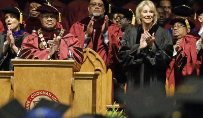 Bethune-Cookman University president Edison Jackson, left, and U.S. Education Secretary Betsy DeVos applaud students as they are introduced during commencement exercises, Wednesday, May 10, 2017, in Daytona Beach, Fla. (AP Photo/John Raoux)