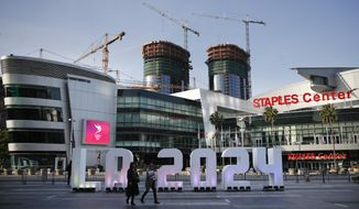 A Los Angeles 2024 sign stands in front of Staples Center Thursday, May 11, 2017, in Los Angeles. After bidding for the 2024 Olympics, Los Angeles might have to wait. With the competition down to LA and Paris, International Olympic Committee leaders are considering a proposal to award the next two Olympics, 2024 and 2028, one to each city. (AP Photo/Jae C. Hong)
