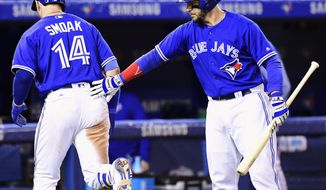 Toronto Blue Jays' Justin Smoak (14) is congratulated by Steve Pearce after hitting a home run against the Seattle Mariners during the seventh inning of a baseball game in Toronto on Thursday, May 11, 2017. (Frank Gunn/The Canadian Press via AP)