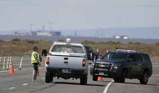 In this Tuesday, May 9, 2017, photo, a Hanford Patrol officer blocks traffic on Route 4S that leads to 200 East Area, where an emergency has been declared at the Hanford nuclear weapons complex in southeastern Washington. The collapse of a tunnel containing radioactive waste at Hanford underscored what critics have long been saying: that the toxic remnants of the Cold War are being stored in haphazard and unsafe conditions, and time is running out to deal with the problem. (Colin Mulvany/The Spokesman-Review via AP)