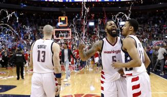 Washington Wizards center Marcin Gortat (13), from Poland, walks off as Markieff Morris (5) and forward Otto Porter Jr. (22) celebrate after Game 6 of an NBA basketball second-round playoff series against the Boston Celtics, Friday, May 12, 2017, in Washington. The Wizards won 92-91. (AP Photo/Alex Brandon)