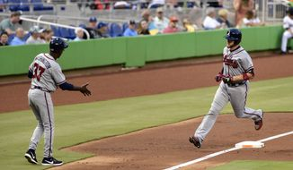 Atlanta Braves' Tyler Flowers, right, rounds third after hitting a home run in the second inning of a baseball game against the Miami Marlins, Friday, May 12, 2017, in Miami. (AP Photo/Gaston De Cardenas)