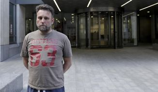Patrick Ward, 47, a sales director at Purbeck Ice Cream, from Dorset in England, poses for photographs after giving media interviews after his heart operation scheduled today was cancelled because of a cyberattack, outside St Bartholomew's Hospital in London, Friday, May 12, 2017. A large cyberattack crippled computer systems at hospitals across England on Friday, with appointments canceled, phone lines down and patients turned away. (AP Photo/Matt Dunham)