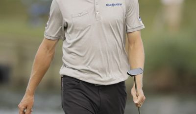 Mackenzie Hughes, of Canada, walks to retrieve his ball on the 17th green, during the first round of The Players Championship golf tournament Thursday, May 11, 2017, in Ponte Vedra Beach, Fla. (AP Photo/Chris O'Meara)