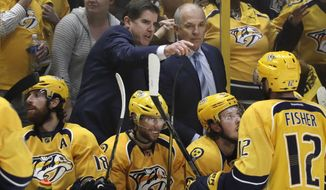 FILE - In this May 7, 2017, file photo, Nashville Predators coach Peter Laviolette, top left, talks with assistant coach Kevin McCarthy during the team's 3-1 win over the St. Louis Blues in Game 6 of a second-round NHL hockey playoff series in Nashville, Tenn. Laviolette is just the third coach since the NHL split its playoffs between conferences in 1994 to take three different teams to a conference final, joining Ken Hitchcock (Dallas, Philadelphia and St. Louis) and Darryl Sutter (Chicago, Calgary and Los Angeles). If the Predators get past Anaheim in the Western Conference finals, which start Friday night, he would be the first in that span to take three different teams to the Stanley Cup Finals. (AP Photo/Mark Humphrey, File)