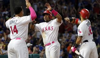 Texas Rangers' Carlos Gomez (14) and Rougned Odor (12) celebrate with Elvis Andrus, center, who scored on a two-run double by Nomar Mazara during the seventh inning of a baseball game against the Oakland Athletics on Saturday, May 13, 2017, in Arlington, Texas. (AP Photo/Tony Gutierrez)