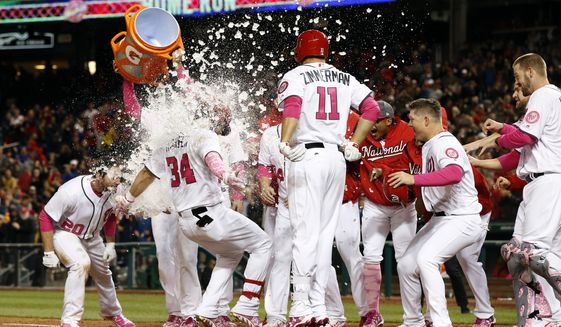 Washington Nationals' Bryce Harper (34) is doused as he scores on his game-winning two-run homer during the ninth inning of a baseball game against the Philadelphia Phillies at Nationals Park on  Saturday, May 13, 2017, in Washington. The Nationals won 6-4. (AP Photo/Alex Brandon)